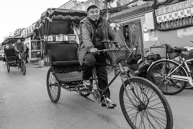 Morgan: Picture of a man riding a rickshaw through a Beijing hutong.