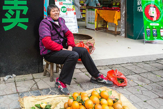 Yangshuo: Picture of orange salesperson.