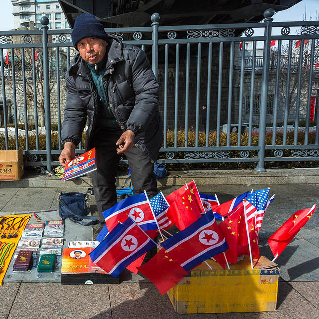 2016: Picture of man under the Friendship Bridge in Dandong, China, selling North Korean flags and money.