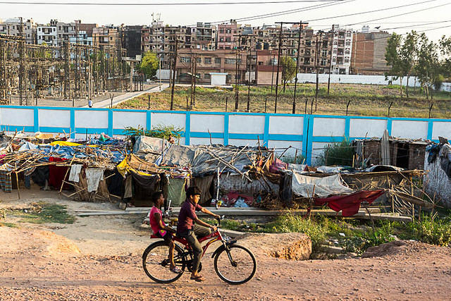 Two boys on a bicycle in front of some slums in Delhi, India.