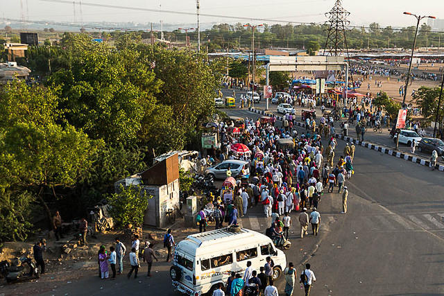 A large crowd forms in Delhi, India.