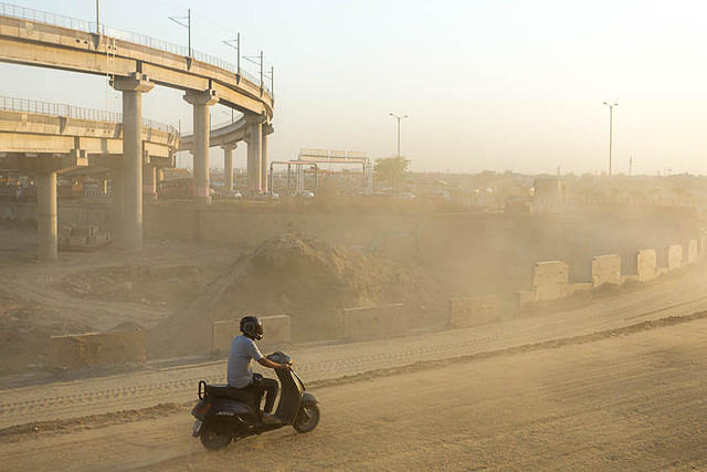India: Picture of a motorcycle on a dusty road in Delhi, India.
