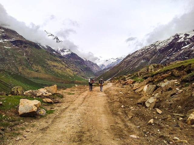 India: Picture of two people hiking on the gravel road to Chattru, India.