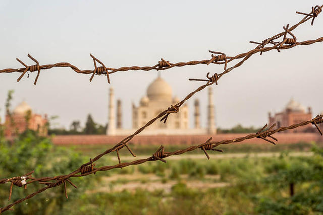 Picture of Taj Mahal behind a barbed wire fence..