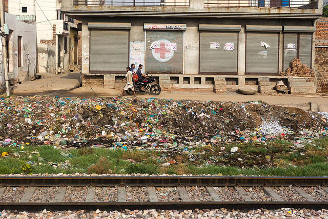 India: Picture of a trash dump next to the train tracks in Delhi, India.