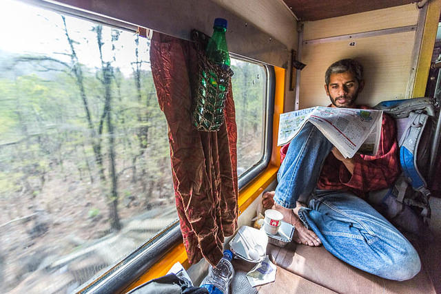 India: Picture of man reading a newspaper on an Indian sleeper train.