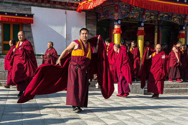 Chain Fail: Picture of monks in red robes exiting a monastery in China.