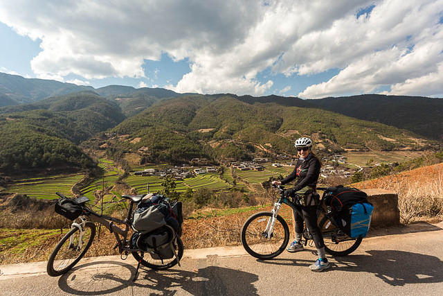 Chain Fail: Picture of Katie riding a bicycle in a valley in Yunnan, China.