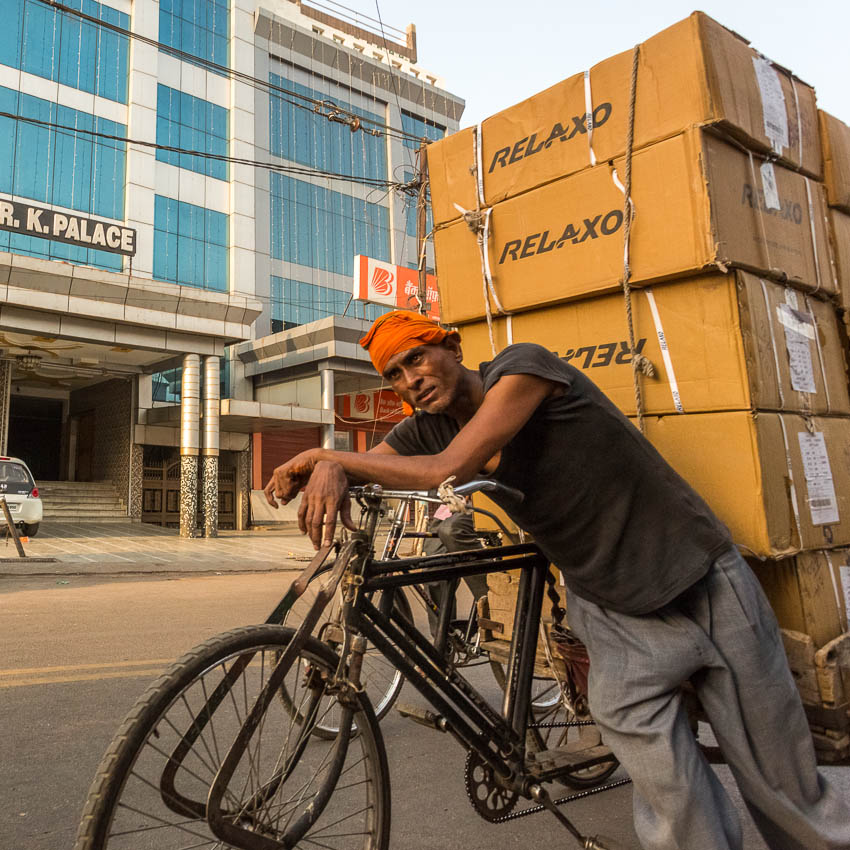 Picture of man pushing heavy load on his bike in India.