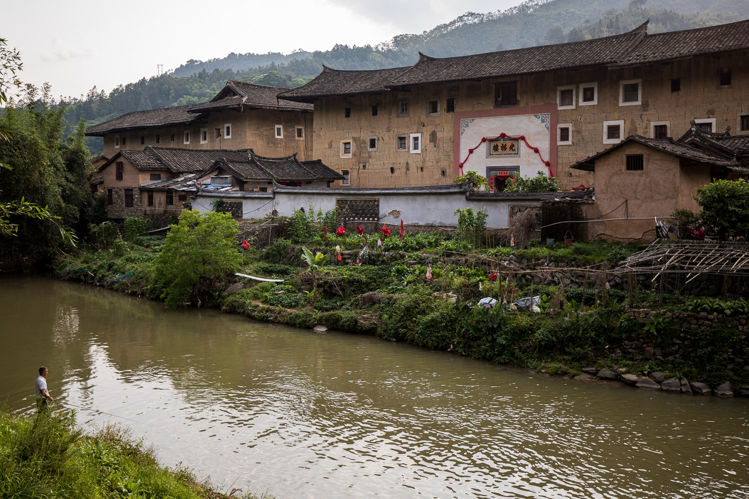 Picture of man fishing in front of tulou building.