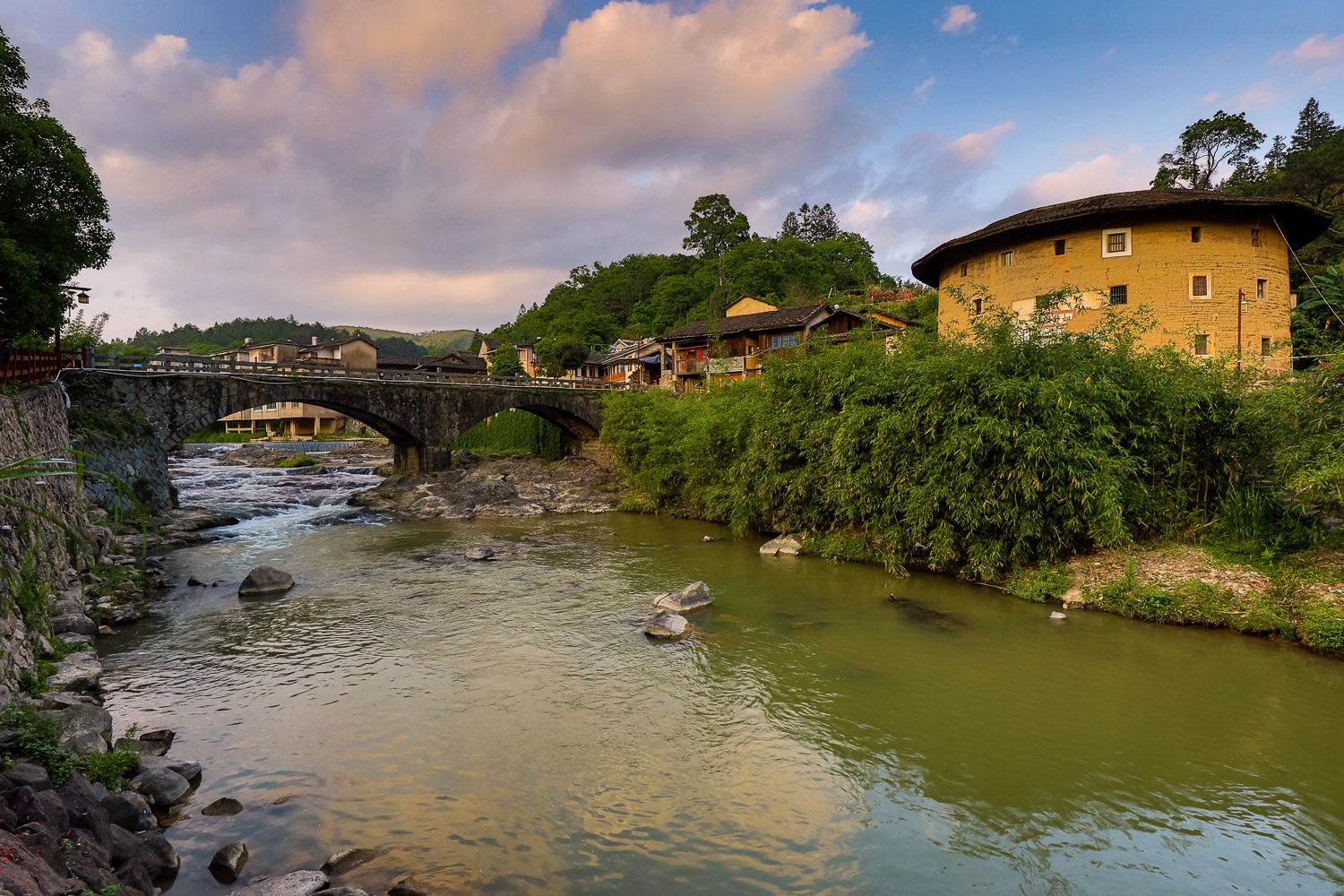 Picture of sunset on the river, with tulou building.